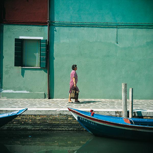 Farbe in der Architektur türkisfarbene Häuserwände in Burano davor eine Frau in einem gepunkteten Kleic