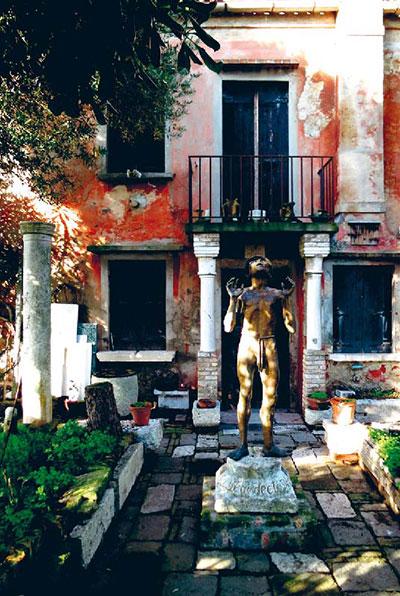 Farbige Häuserwand auf Burano davor eine Götterskulptur und dorische Säulen